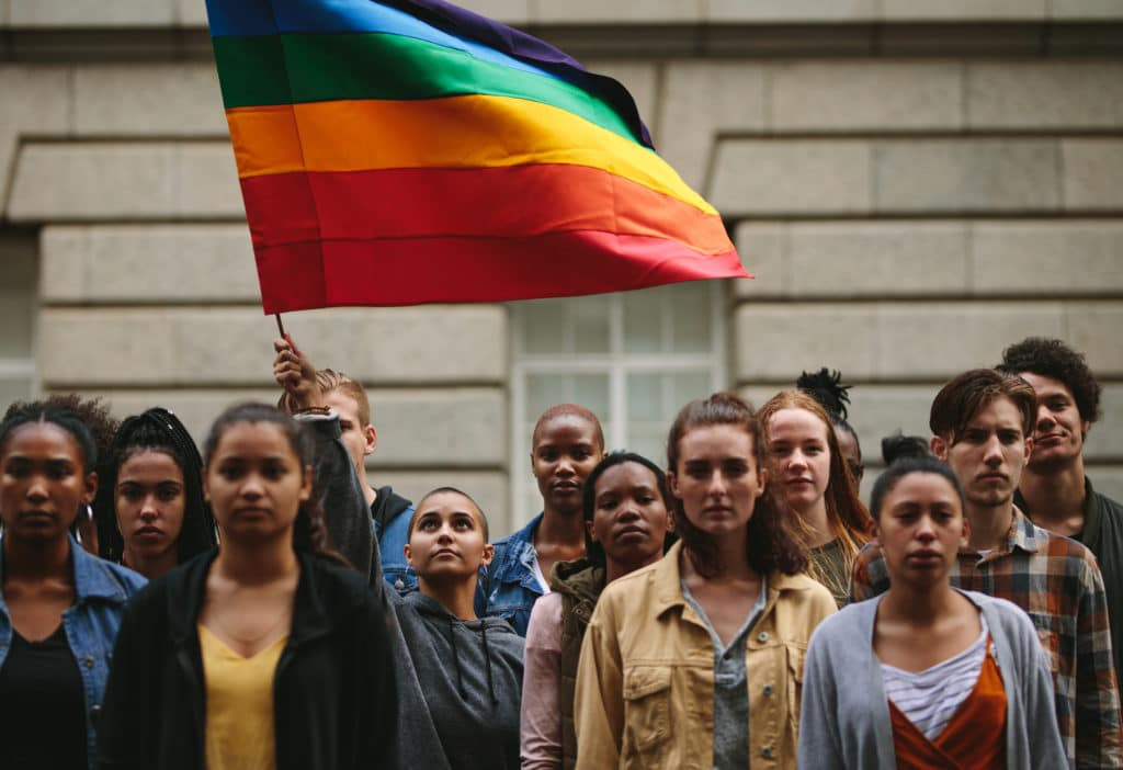 LGBTQ youth look solemn while one raises pride flag