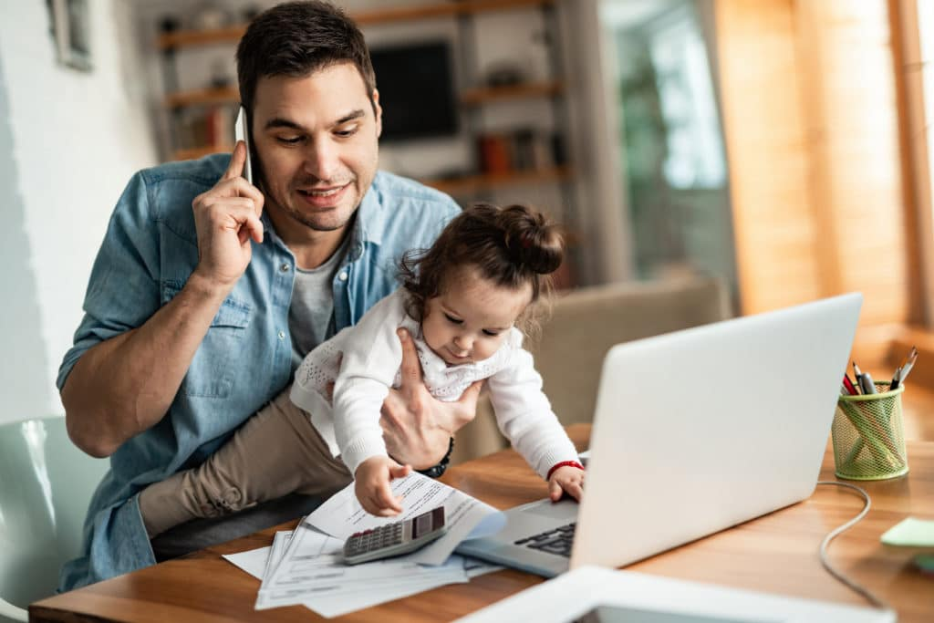 Man working from home with his child on his lap