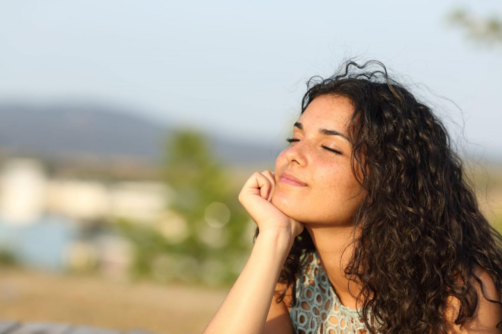 Young woman looks content and mindful