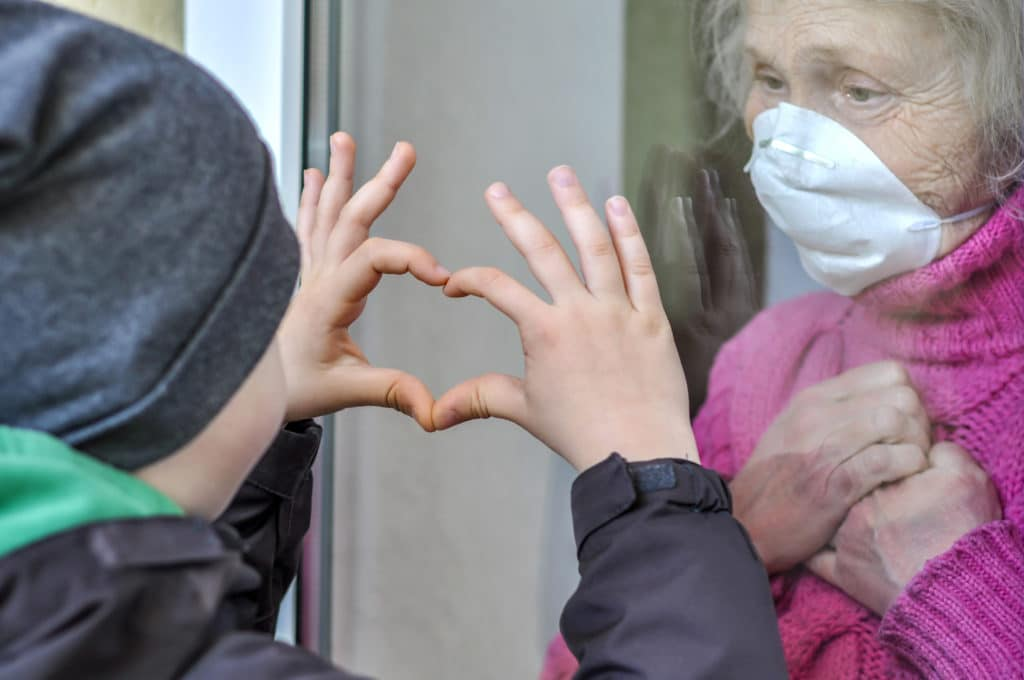 grandmother in mask and grandson show love through a window