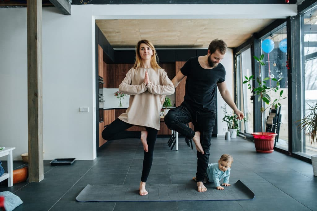 happy couple practices yoga at home while toddler crawls