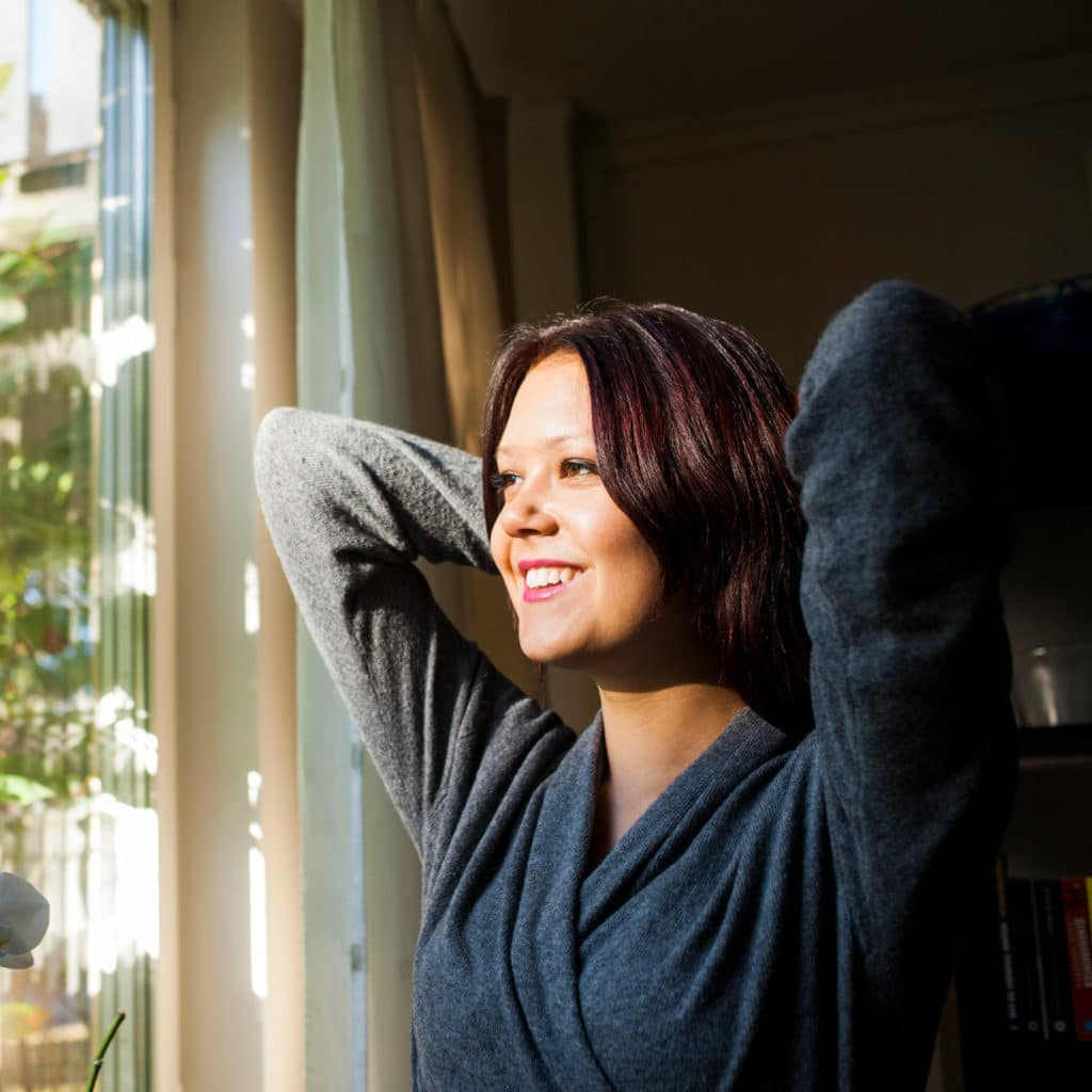 Happy woman looking through a window