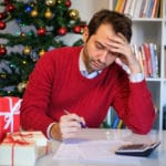 man uses pen and calculator gifts and tree in background