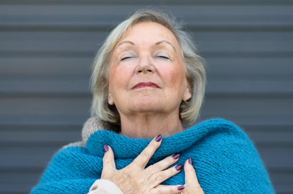 Older woman takes deep breath for relaxation