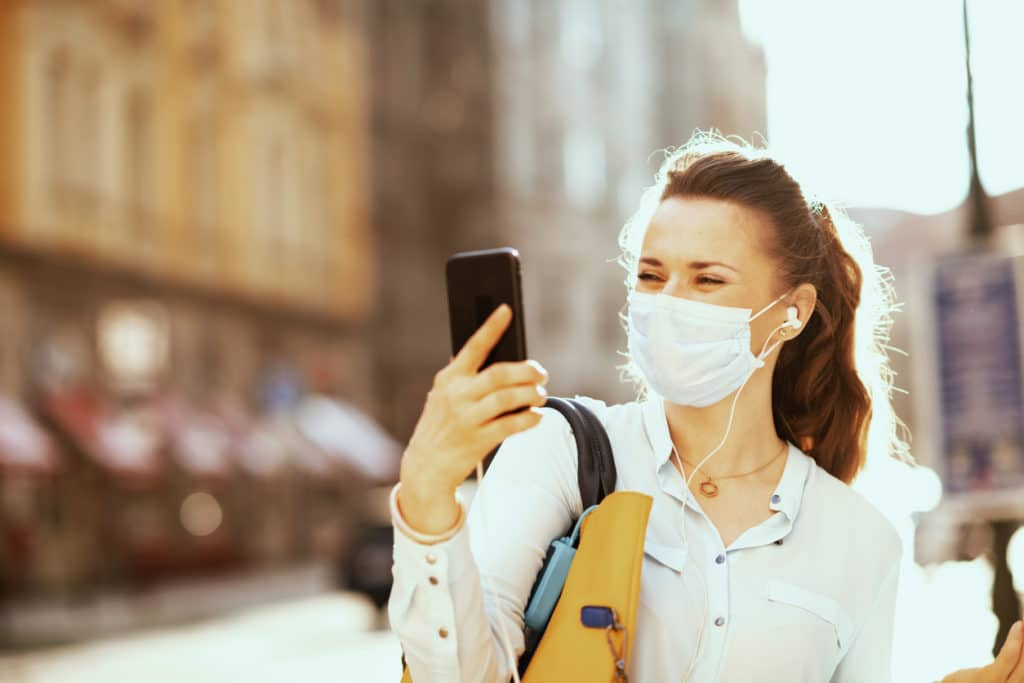 woman in blue blouse with medical mask, handbag and disinfectant having video conference outdoors