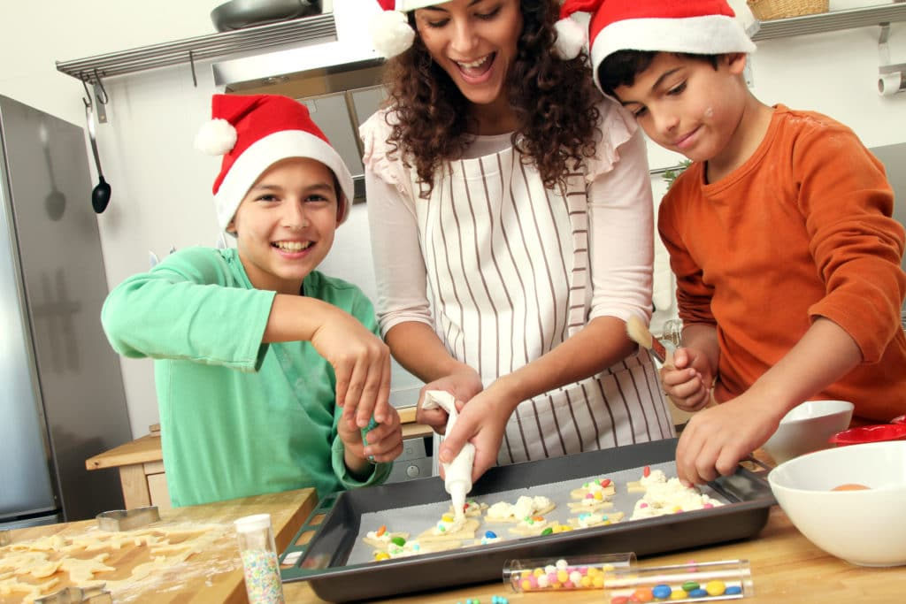 woman bakes holiday cookies with two boys