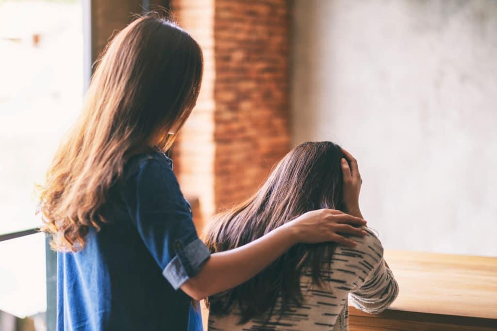 woman comforts friend arm on shoulder