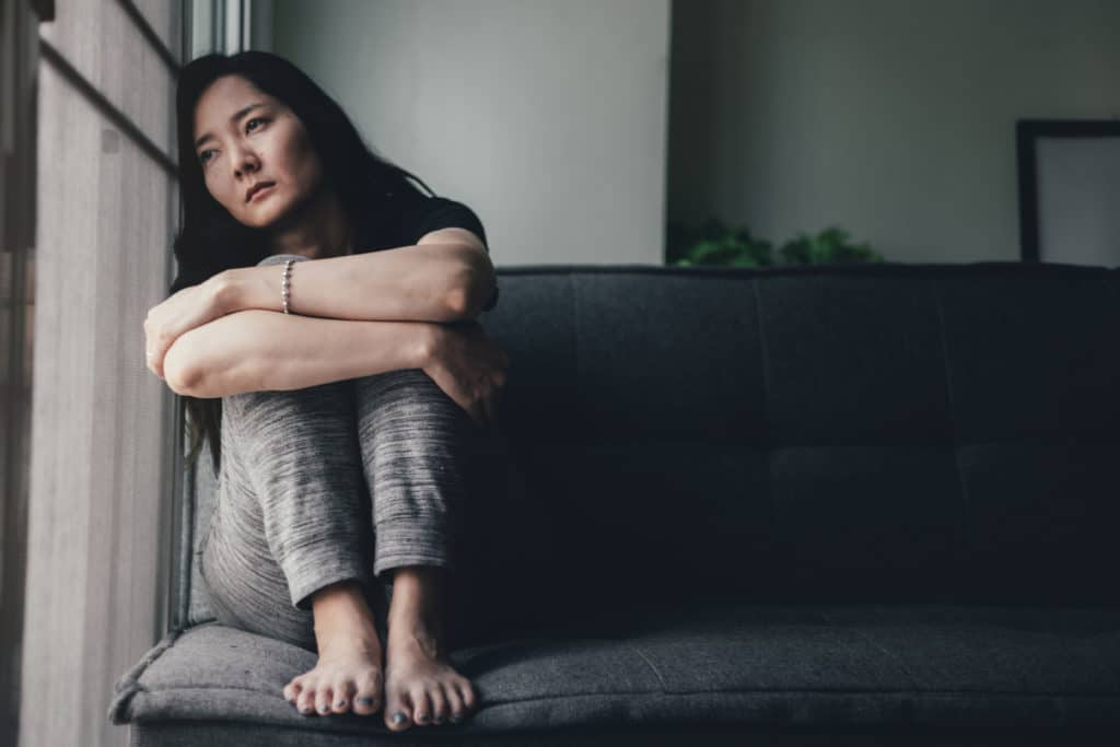 woman curls up on couch and looks out window