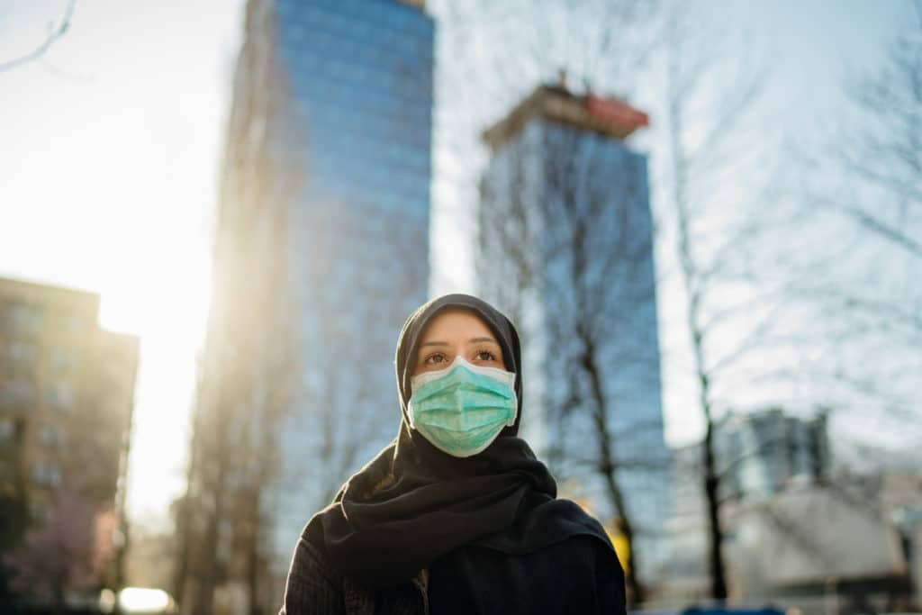 woman in hijab and mask walks in city