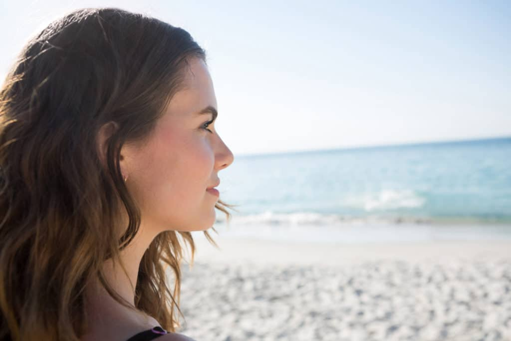 woman looks toward ocean with optimism and determination