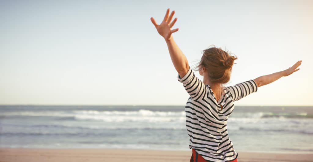woman stands on beach with arms open wide