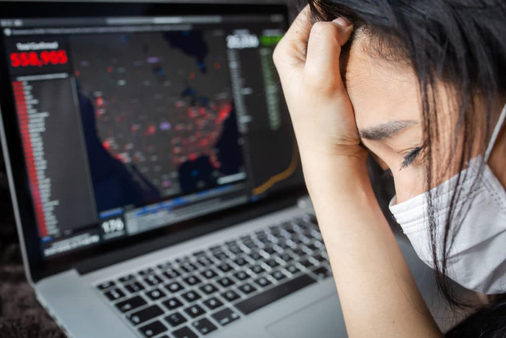 woman with mask on looks at covid map and cries
