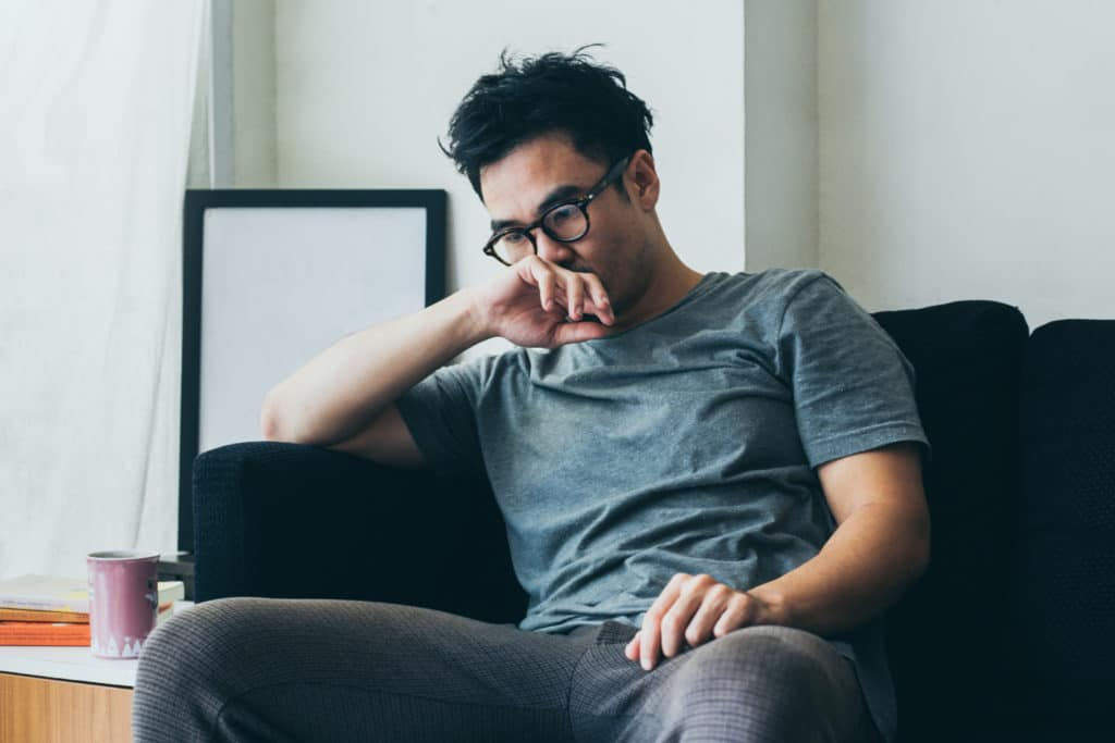 Young man sits on couch battling depression and trauma